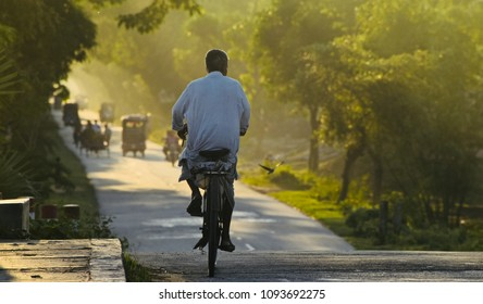 A poor old man is riding a bicycle on the urban streets in the afternoon unique photograph