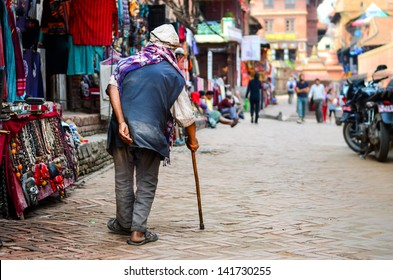 Poor old man walking with stick in exotic asian street, Nepal