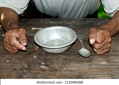 Poor old man's hands and empty bowl on wooden background.An angry hungry man clenches his hands into fists. the concept of hunger or poverty. Selective focus.Homeless. Alms