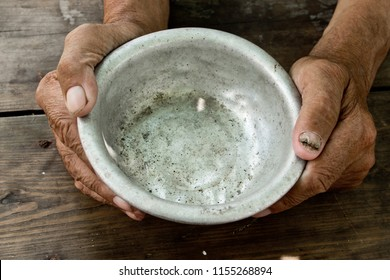 The poor old man's hands hold an empty bowl of beg you for help. The concept of hunger or poverty. Selective focus. Poverty in retirement. Alms