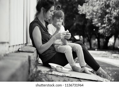 Poor people eating donated food on street, black and white effect