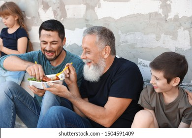 Poor people holding plates with food near wall outdoors