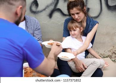 Poor people receiving food from volunteer outdoors