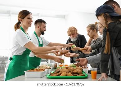Poor people receiving food from volunteers indoors