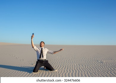 Poor signal. Frustrated young businessman searching for mobile phone signal while sitting on sand in desert
