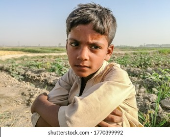 a poor staring hungry orphan boy and sad expression on his face and his face and clothes are dirty and his eyes are full of pain
