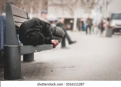 Arme Obdachlose oder Flüchtlinge schlafen auf der Holzbank auf der städtischen Straße in der Stadt, soziales Dokumentarkonzept, selektiver Fokus