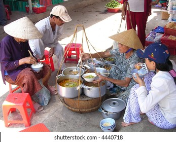 poor vietnamese having meal in front of the street food vendor: typical lifestyle
