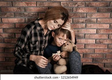 Poor woman hugging her son near brick wall
