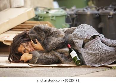 poor woman tramp lying among bin with wine bottle