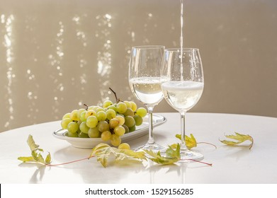 Pooring wine into glasses with muscat grapes and autumn leaves