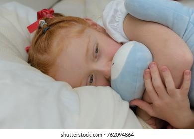 Poorly little girl lying in bed cuddling her teddy.