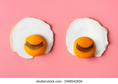 Pop art background. fried egg with eyelashes on a pinkbackground. Food art. Morning concept of face