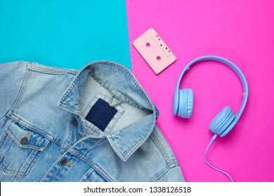 Pop culture attributes eighties. Denim jacket, headphones, audio cassette on a blue-pink background. Top view, 80s
