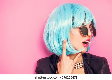 Pop girl portrait wearing blue wig and making the horns