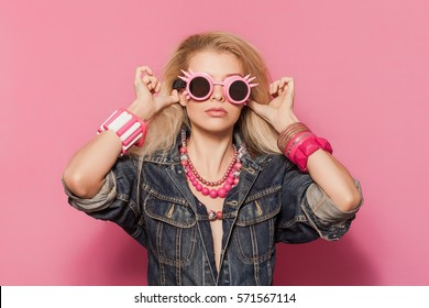 Pop girl portrait wearing jeans jacket and odd sunglasses
