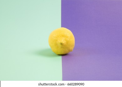 Pop minimal still life photography. lemon isolated on a Pop minimal still life photography. Lemon yellow isolated on a purple background bicolor purple and turquoise background