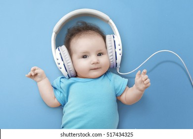 Pop music. Happy smiling newborn baby listens to music in headphones on  blue background