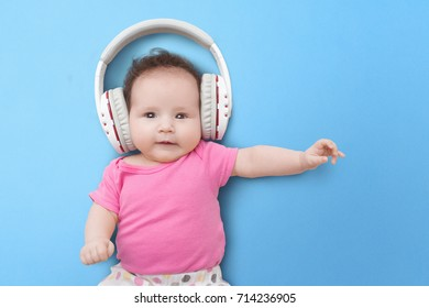 Pop music. Happy smiling newborn baby  listens to music in headphones on  blue background. Cheerful children's portrait