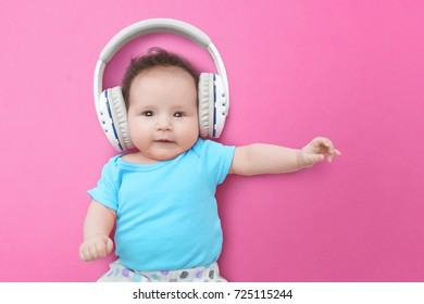 Pop music. Happy smiling newborn baby  listens to music in headphones on pink background. Cheerful children's portrait