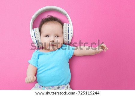 Pop Music Happy Smiling Newborn Baby Listens To Music In Headphones On Pink Background
