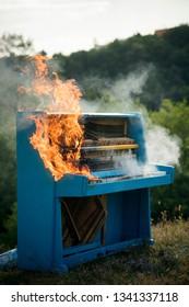 Pop music, melody, rhapsody, looting. Piano on fire, keyboard, smoke. Fire, art, Halloween, trash bonfire Burning piano musical style grunge instrument Rock concert jazz fireplace destruction