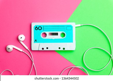 Pop music style attributes eighties, retro old school 80-s or 90-s concept. Audio cassette on a bright blue-pink creative background