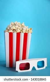 Popcorn and 3D glasses on blue background