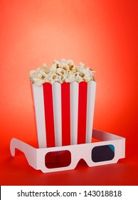 Popcorn and 3D glasses on red background