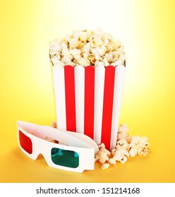 Popcorn and 3D glasses on yellow background