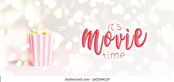 Popcorn bag with white and pink stripes at the festive lights bokeh backdrop. Romantic movie night and snack concept with It's movie time wording. Banner wide screen format