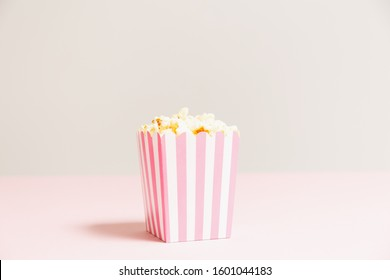 Popcorn bag with white and pink stripes at the light neutral backdrop. Empty minimalistic background. Romantic movie night and snack concept. Horizontal