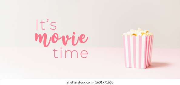 Popcorn bag with white and pink stripes at the light neutral backdrop. Empty minimalistic background. Romantic movie night and snack concept with It's movie time wording. Banner wide screen format