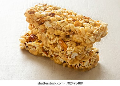 Popcorn bar with almonds and pretzel pieces dipped in smooth salted caramel flavoured coating