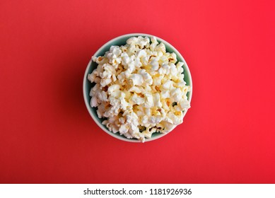 Popcorn in a bowl on red background, top view