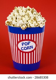A popcorn bucket over a red background.