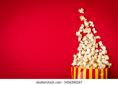 Popcorn with caramel on red background.