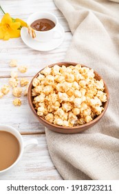 Popcorn with caramel in wooden bowl and a cup of coffee on a white wooden background and linen textile. Side view, close up.