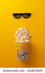 Popcorn in a carboard box and 3D glasses over yellow background