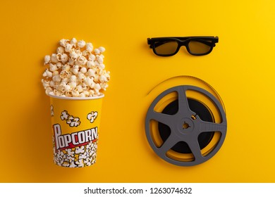 Popcorn in a carboard box, glasses and film roll over yellow background