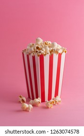 Popcorn in a carboard box over pink background