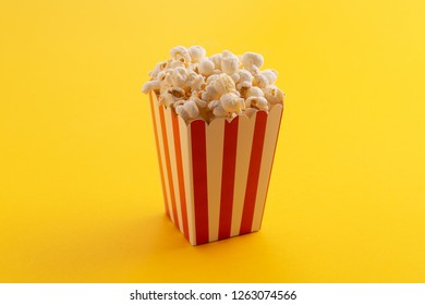 Popcorn in a carboard box over yellow background