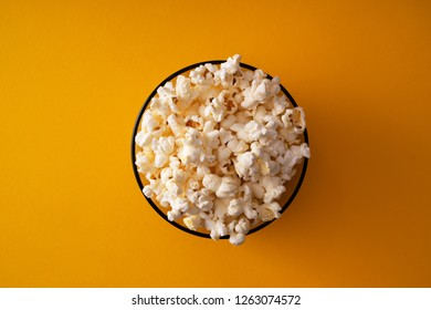 Popcorn in carboard box over yellow background
