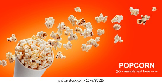 Popcorn in cardboard box, isolated on red background with copy space