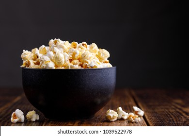 Popcorn in a ceramic bowl and scattered on a wooden background. Side view.