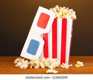 popcorn and cinema glasses on wooden table on brown background