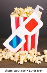 popcorn and cinema glasses on wooden table on grey background
