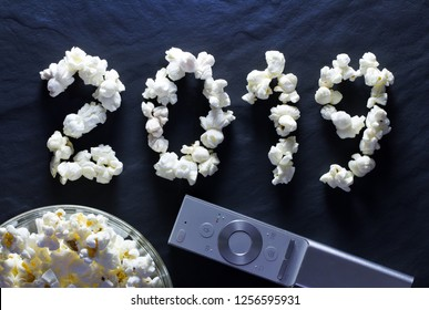 Popcorn closeup in the form of the number 2019 and the remote control from the TV on a dark background. Christmas and New Year holidays at home by the TV