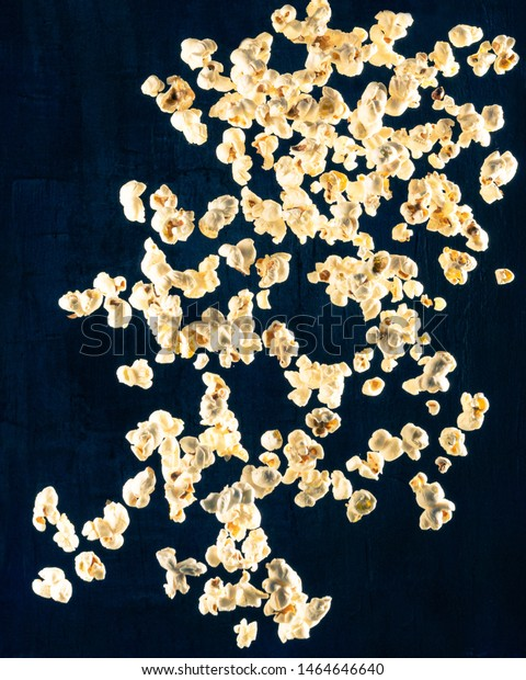 Popcorn dropping from top to bottom in front of blue textured backdrop