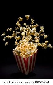 Popcorn exploding from inside the popcorn box
